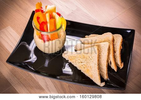 Breakfast with toasts, slices of vegetables and creamy hummus dip
