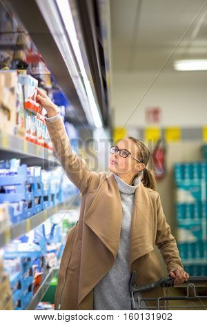 Beautiful young woman shopping for groceries and fruits and vegetables in produce department as well as some lactose free diary products in a grocery store/supermarket (color toned image; shallow DOF)
