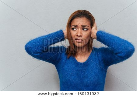 Young displeased african woman in sweater shutting her ears and not listening as well as looking aside. Isolated gray background