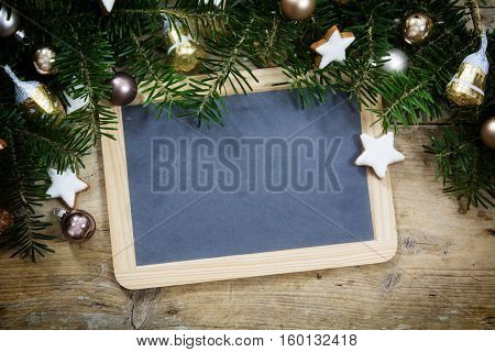 Slate writing board with fir tree branches christmas balls and cookies on a rustic wooden board holiday background frame with copy space
