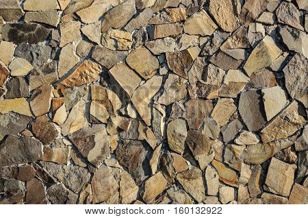 Fragment of decorative brown facing of stone wall surface