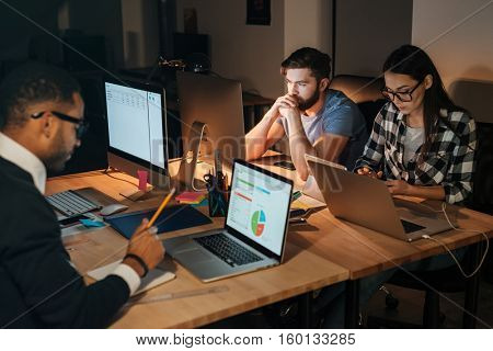 Photo of three business people working late at night in their office.