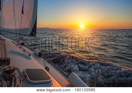 Sailing boat during amazing sunset on the sea.