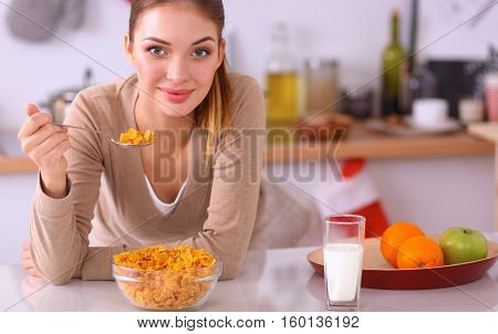Smiling woman having breakfast in kitchen interior