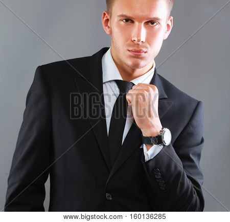Portrait of a successful young business man standing isolated on grey background.