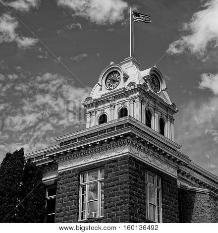 An American Flag flies proudly at the top of the historic Crook County Courthouse in Central Oregon on a sunny summer afternoon.