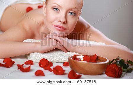 Beautiful young woman getting spa massage, lying.