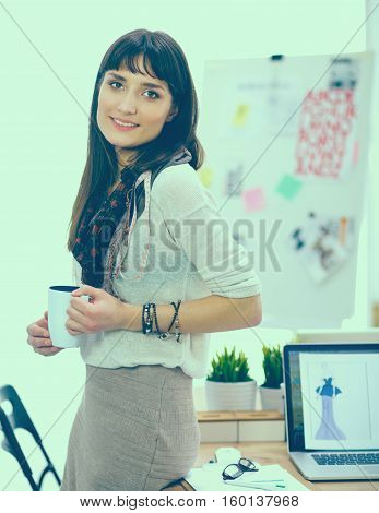 Young attractive fashion designer standing by desk in office, holding cup.