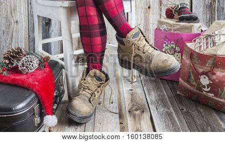 horizontal image of  woman sitting on chair with only  legs showing wearing a pair of red and black checkered leotards and wearing big old work shoes with a suitcase and gift bags  on floor