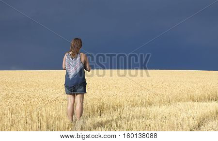 horizontal image of a caucasian woman standing in a field of golden wheat looking toward the sky which is very dark with a thunder storm coming.