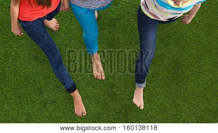 Three women with naked feet standing in grass .