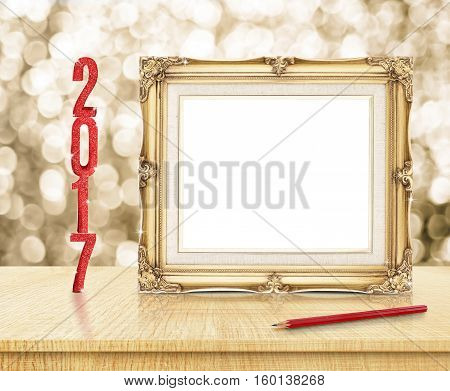Blank Golden Vintage frame with red glitter 2017 new year and red pencil with sparkling gold bokeh wall and wooden tableMock up for adding your text or design.(3d rendering)