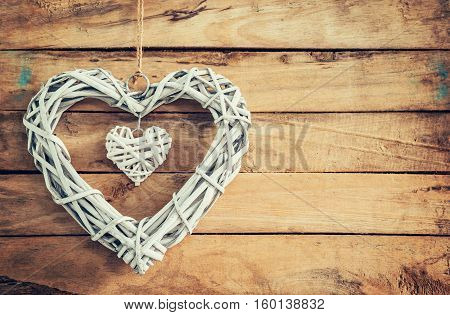 Two wooden rustic decorative hearts hanging on vintage wooden background with space.