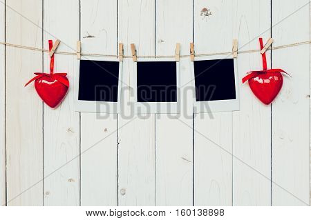 Three Photo Frame Blank And Red Heart Hanging On White Wood Background With Space