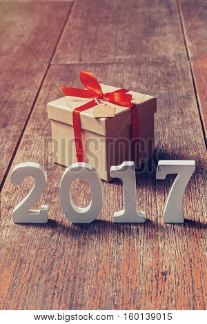 Wooden Numbers Forming The Number 2017, For The New Year 2017 On Rustic Wooden With Gift Box And Red