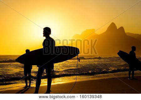 Silhouettes of surfers holding their surfboards on the background of golden sunset on Ipanema Beach and Two Brothers, Dois Irmaos Mountain, Rio de Janeiro, Brazil