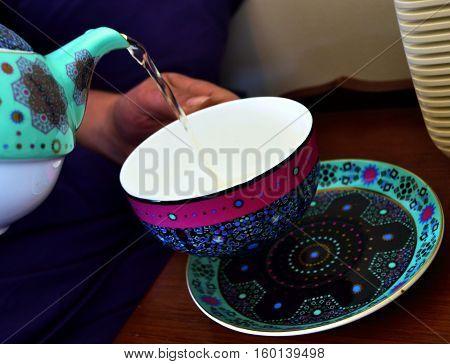 teapot pouring tea into a tea cup