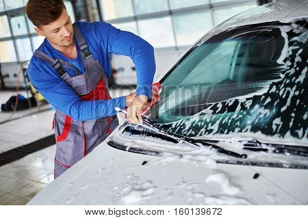 Man worker washing windshield with sponge on a car wash.
