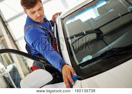 Man worker polishing car on a car wash.