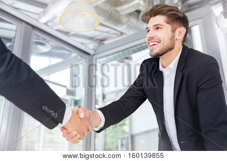 Two smiling successful young businessmen shaking hands on business meeting in office