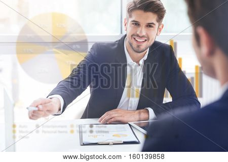 Double exposure of Two smiling young businessmen working on business meeting in office
