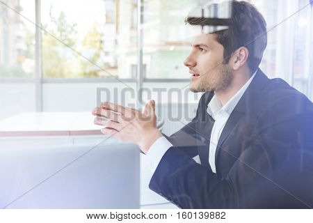 Handsome young businessman in black suit sitting in office
