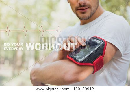 Young man athlete using mobile phone in handband outdoors in the morning. Do your workout everyday