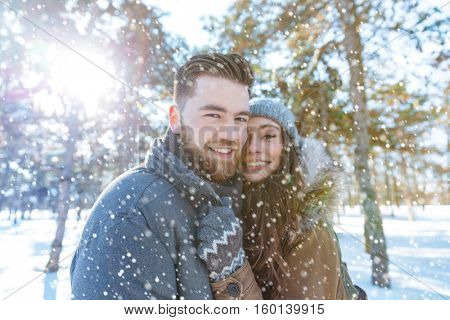Happy young couple standing in winter park and looking at camera