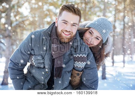 Happy beautiful couple standing in winter park and looking at camera