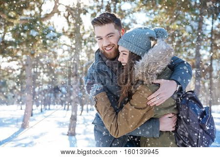 Smiling young couple hugging in winter park