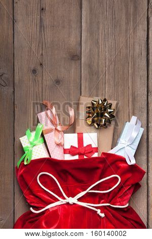 Santa Claus Bag Full By Present Gift Box, Red Christmas Sack on Brown Wood Wall Background
