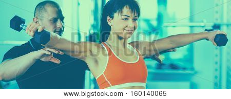 Beautiful woman at the gym exercising with her trainer .