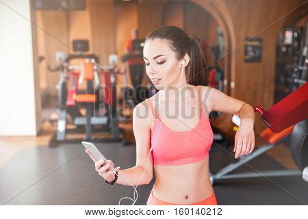 Smiling charming young woman athlete in earphones using smartphone and listening to music in gym