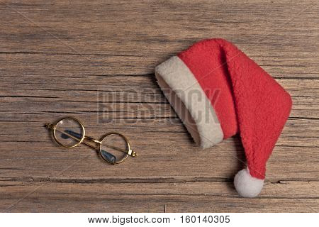 Santa red hat and golden spectacles on wooden background, holiday Christmas