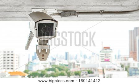 Security equipment concept - Close up indoor CCTV camera surveillance on ceiling of car parking Safety system area control with tower background and copy space