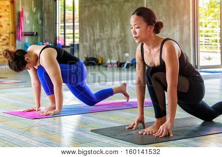 Asian trainee strong woman practicing difficult yoga pose in classroom