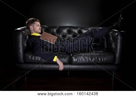 Fashionable student or research academic sleeping on a couch with a book. Fell asleep reading or studying.