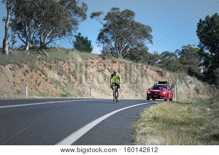 Jindabyne, Snowy Mountains Region, Australia - December 3, 2016: The first L'Etape cycling event held in Australia (by Le Tour de France).  A competitor and race official car in the 2nd race stage.