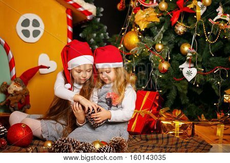 Two sisters waiting for Christmas. Girls sitting on the floor next to a Christmas tree and presents. Santa hat on their heads. Family celebration. Happy childhood.