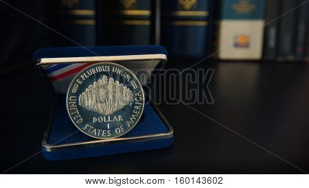 Commemorative 1 dollar silver coin on a black table with binders and book in the background - Numismatic Scene