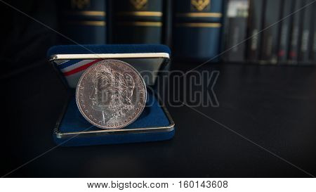 Old 1 dollar silver coin on a black table with binders and book in the background - Numismatic scene