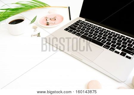 Flat lay top view office table desk. Workspace with laptop palm branch coffee cup and clips on white background.