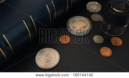Different American coins on black table with magnifying glass and album for coins - Numismatic scene
