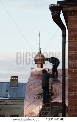 KAZAN, RUSSIA, 19 NOVEMBER 2016, two workers Roofer repairing roof of ortodox Old believers ' Church in winter cold day, horizontal