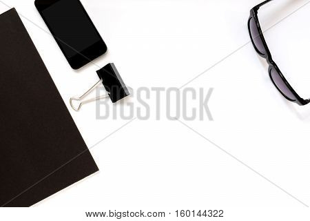 Flat lay photo of office desk with black book smartphone eyeglasses and paper clip with copy space background