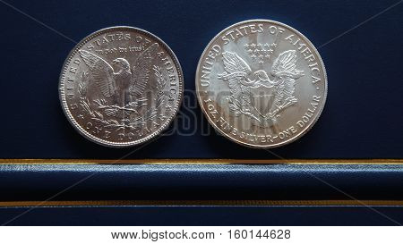 Old American silver dollar and new American silver dollar on blue background - Numismatic scene