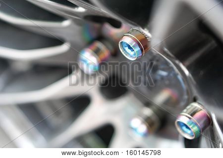 Car wheel and tire concept - Close up decoration nut of alloy wheel mag on black car