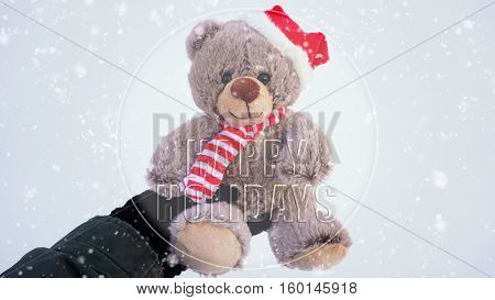 Female hand holding a cute Christmas teddy bear against snow on the ground with snowfall effect with words Happy Holidays