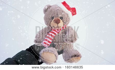 Female hand holding a cute Christmas teddy bear against snow on the ground with snowfall effect with words Merry Christmas