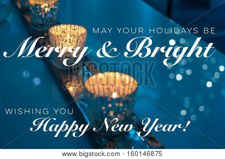 "Happy holidays card with words ""May your holidays be merry &bright"" and ""Wishing you a Happy New Year"" written on blue sparkling background photography of candles burning bright with gold not religious with space for logo or message"